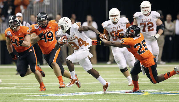 Texas' Marquise Goodwin (84) attempts to break away from Oregon State's Ryan Murphy (25) in the second half of the 2012 Valero Alamo Bowl on Saturday, Dec. 29, 2012. Photo: Kin Man Hui, Express-News / © 2012 San Antonio Express-News