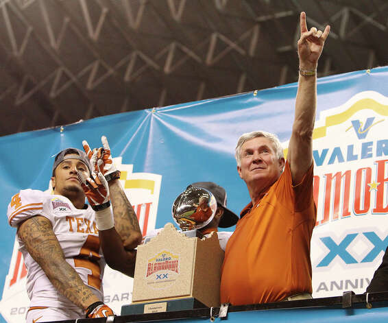 Texas head coach Mack Brown gestures the Longhorn sign along with player Kenny Vaccaro (04) after receiving the 20th Valero Alamo Bowl trophy for defeating Oregon State on Saturday, Dec. 29, 2012. Texas won, 31-27. Photo: Kin Man Hui, Express-News / © 2012 San Antonio Express-News