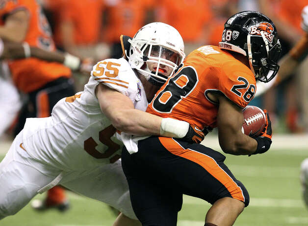 Texas'  Dalton Santos (55) makes a tackle against Oregon State's Terron Ward (28) in the second half of the 2012 Valero Alamo Bowl on Saturday, Dec. 29, 2012. Photo: Kin Man Hui, Express-News / © 2012 San Antonio Express-News
