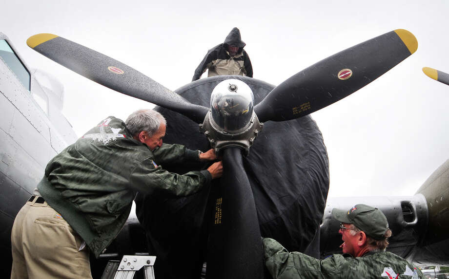 "May 22, 2012— Neil Morrison, left, and two other crew members secure a tarp over an engine of a WWII-era B-17 ""Flying Fortress"" at Seattle's Museum of Flight. Photo: LINDSEY WASSON / SEATTLEPI.COM"