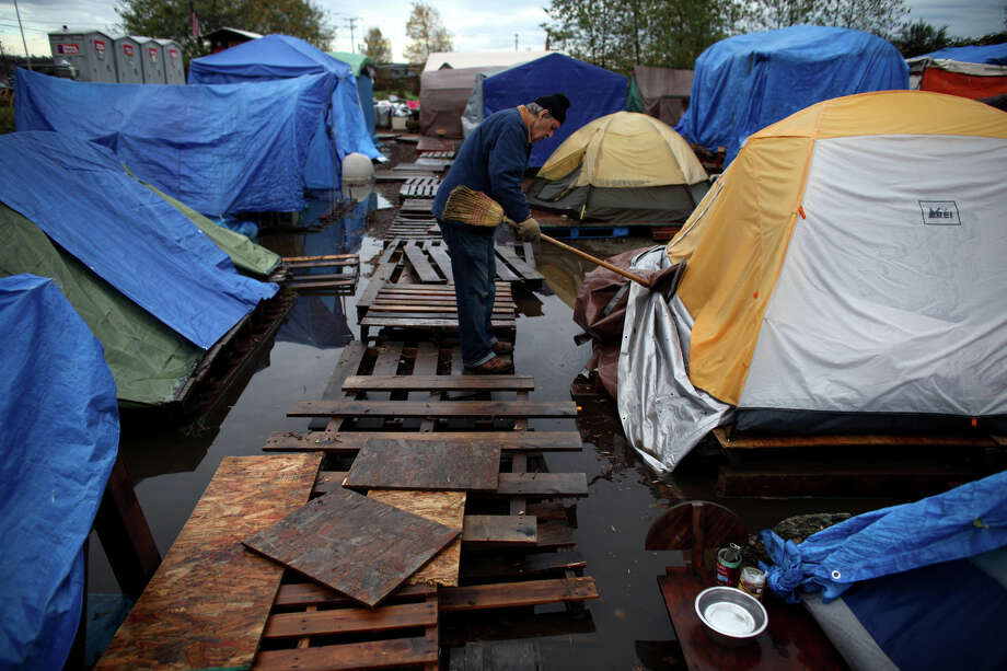 November 20, 2012 — Resident Jim Morgan works to help water flow toward a pump after record rainfall flooded Seattle's Nickelsville homeless camp at 7116 West Marginal Way South. Tents and the pallets they rested on were floating after the camp filled with up to one foot of water. Photo: JOSHUA TRUJILLO / SEATTLEPI.COM