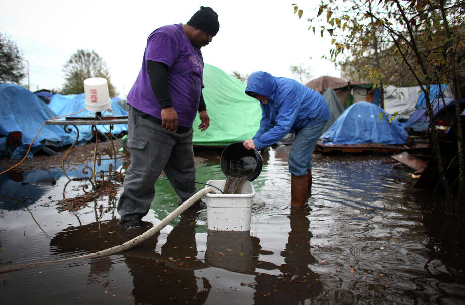 November 20, 2012 — Nickelsville residents work to remove water from the homeless camp after record rainfall flooded the homeless camp at 7116 West Marginal Way South. Tents and the pallets they rested on were floating after the camp filled with up to one foot of water. Photo: JOSHUA TRUJILLO / SEATTLEPI.COM