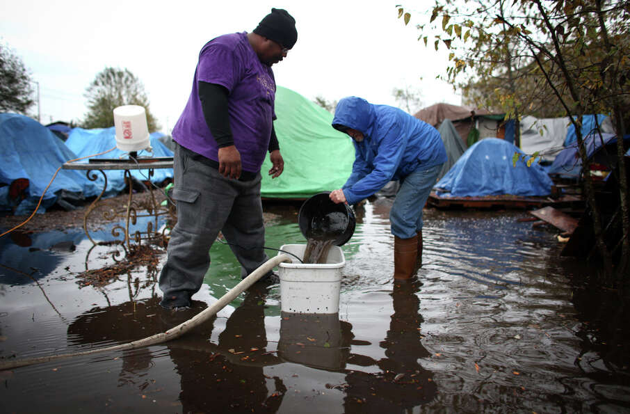 November 20, 2012 — Nickelsville residents work to remove water from the homeless camp afte