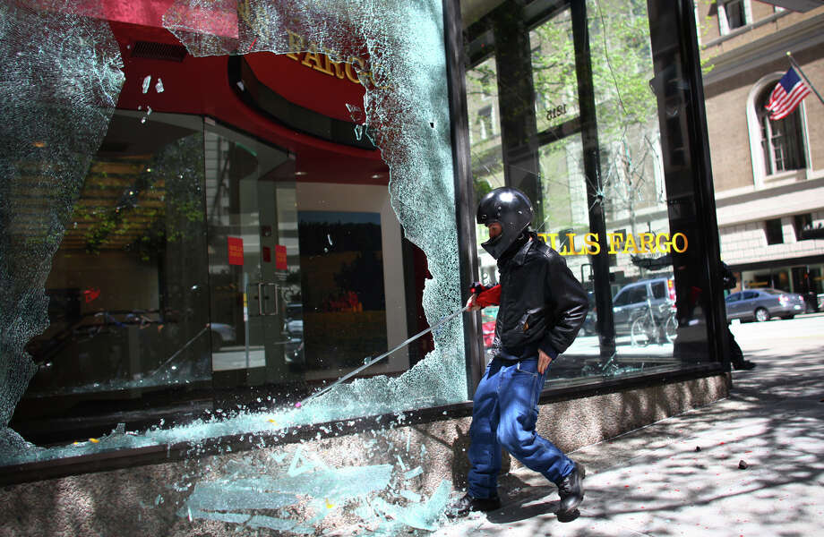 May 1, 2012 — A black-clad protester smashes windows on a Wells Fargo Bank branch during a May Day rally in downtown Seattle. A group of a few dozen protestors caused mayhem in downtown Seattle by smashing windows and vandalizing businesses, cars and the downtown federal courthouse. Investigations later pointed to many of the agitators coming from out of town, with a plan to wreak havoc on Seattle as an expression of their frustration with the government and consumer culture. Photo: JOSHUA TRUJILLO / SEATTLEPI.COM
