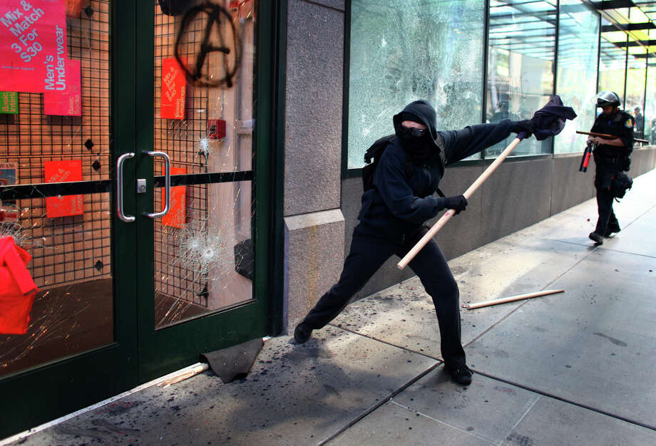 May 1, 2012 — Black-clad protesters break windows on downtown businesses ?including American Apparel and NikeTown? during a May Day rally and march. A group of a few dozen protestors caused mayhem in downtown Seattle by smashing windows and vandalizing businesses, cars and the downtown federal courthouse. Investigations later pointed to many of the agitators coming from out of town, with a plan to wreak havoc on Seattle as an expression of their frustration with the government and consumer culture. Photo: JOSHUA TRUJILLO / SEATTLEPI.COM