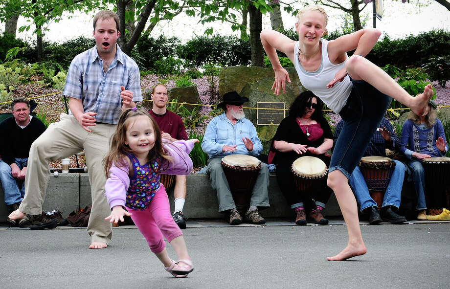 April 28, 2012 — People dance in the middle of a large drum circle at the 19th annual World Rhythm Festival. The free weekend festival featured over 100 performances and drum & dance workshops. Photo: LINDSEY WASSON / SEATTLEPI.COM