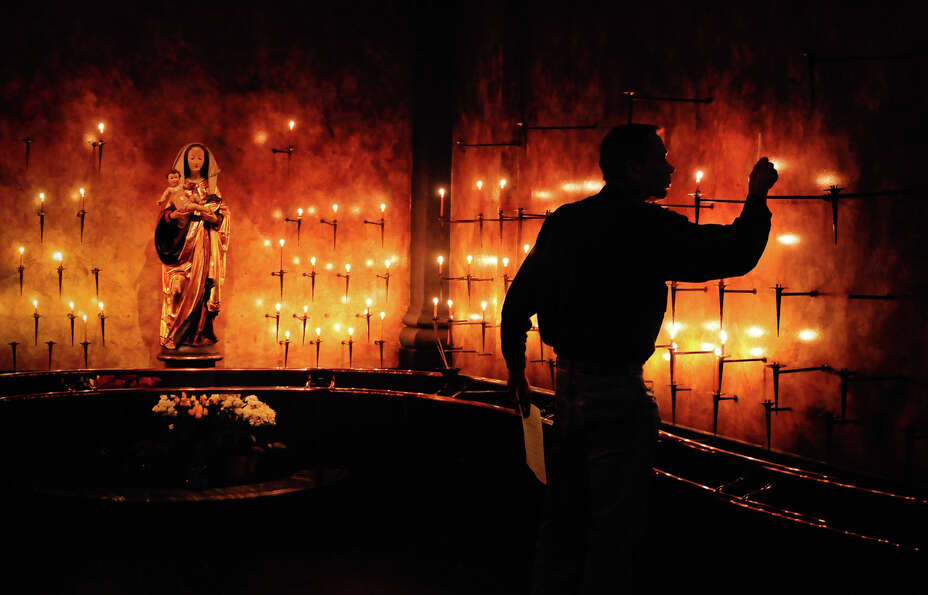 June 1, 2012 — Joseph Stimson lights a candle during a prayer service at St. James Cathedra