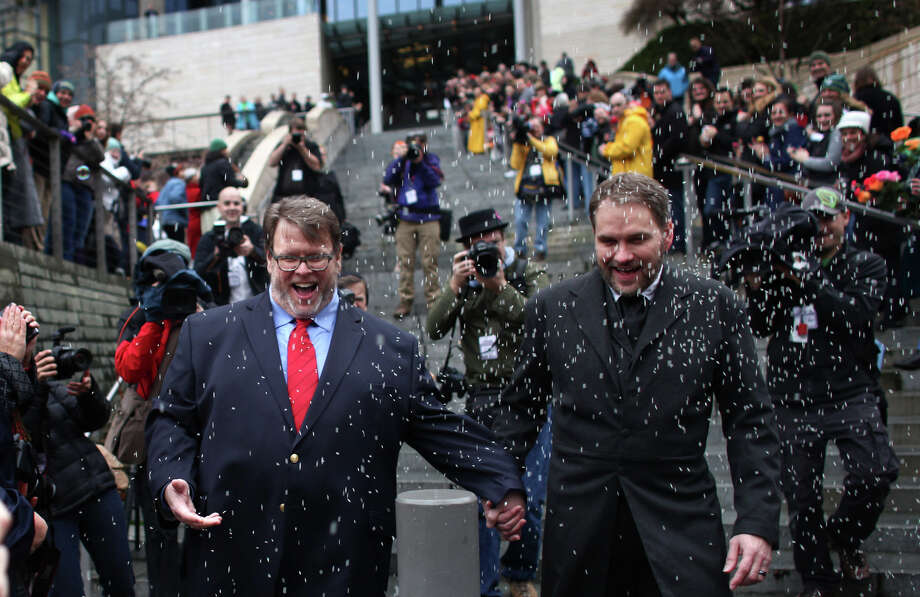 December 9, 2012 — Grant Thornley, left, and Tim Keber are showered with rice as they walk down the stairs of Seattle City Hall after they were married on the first day same-sex couples in Washington State could legally be married. Photo: JOSHUA TRUJILLO / SEATTLEPI.COM