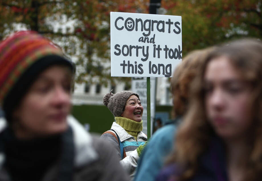 December 9, 2012 — Cindy Ogasawara holds up a sign as newly-married couples walk down the stairs of Seattle City Hall after they were married on the first day same-sex couples in Washington State could legally be married. Photo: JOSHUA TRUJILLO / SEATTLEPI.COM