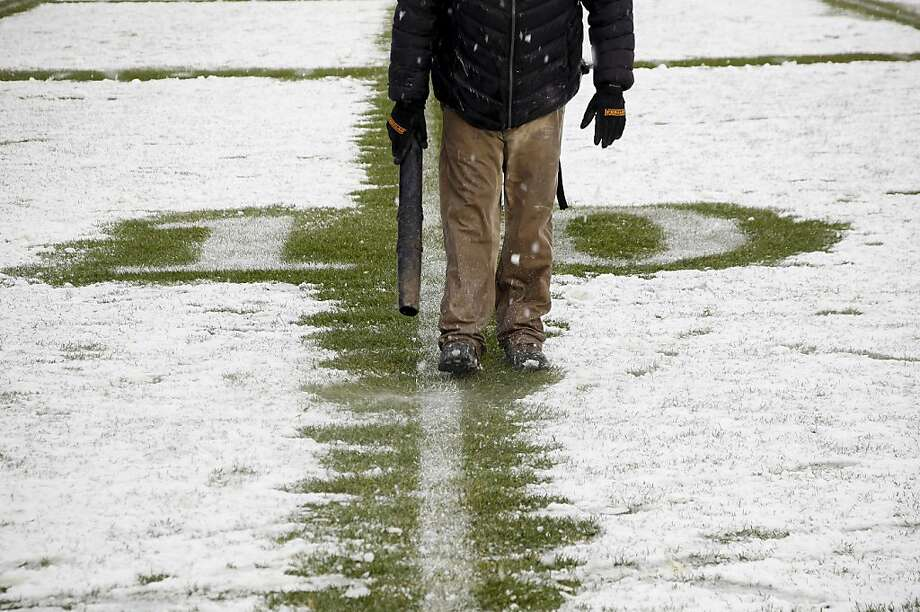 A member of the Yankee Stadium grounds crew clears snow from the 10-yard line before the New Era Pinstripe Bowl between West Virginia Mountaineers and the Syracuse Orange at Yankee Stadium on December 29, 2012 in the Bronx borough of New York City. Photo: Jeff Zelevansky, Getty Images