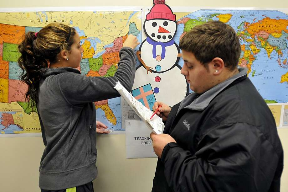 Michael Bardarelli reads off the state while Sabrina Fronte, 14, places a push-in in the maps of the country and world where a parcels for the Snowflakes Project came from at the Connecticut Parent Teacher Student Association, which is collecting the snowflakes to create a Winter Wonderland for the kids of Sandy Hook Elementary School, in Hamden, Connecticut, Friday, December 28, 2012. Photo: John Woike, McClatchy-Tribune News Service