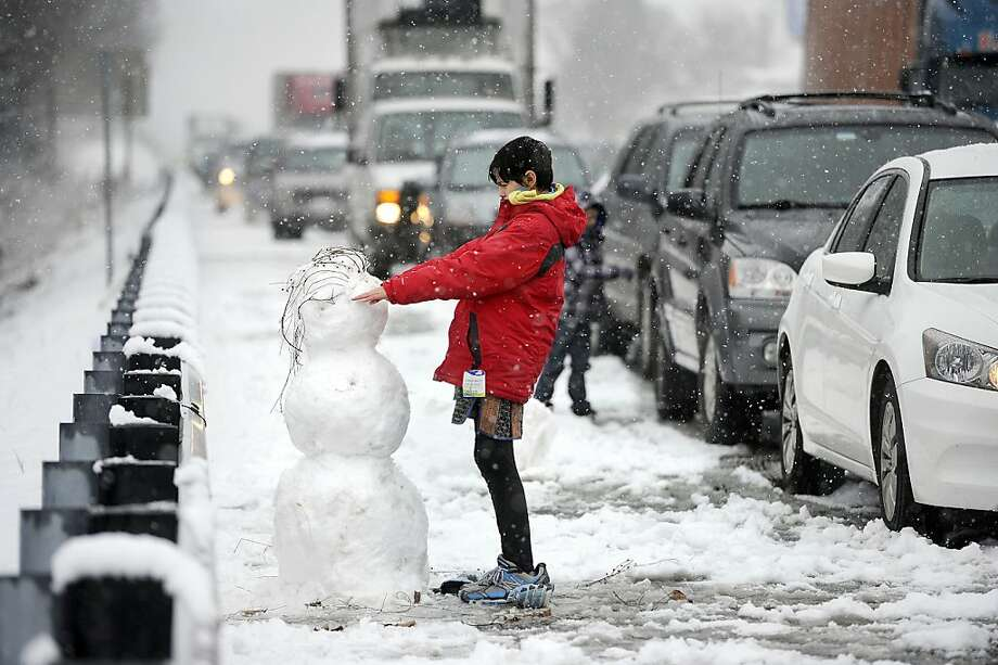 Kristina Waymire, 13, of Baltimore, builds a snowman along the shoulder of Interstate 83 while waiting in stopped traffic for an hour and a half following a 14-vehicle wreck in York, Pa., on Saturday, Dec. 29, 2012. Photo: Jason Plotkin, Associated Press