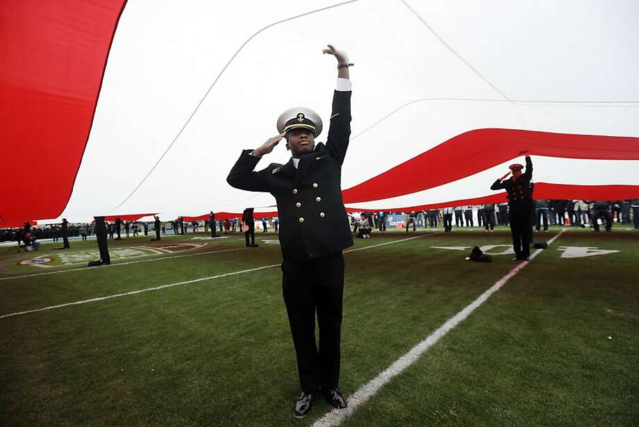 A United States Naval Academy cadet salutes while holding the U.S. flag before the Fight Hunger Bowl NCAA college football game between Navy and Arizona State in San Francisco, Saturday, Dec. 29, 2012. Photo: Marcio Jose Sanchez, Associated Press