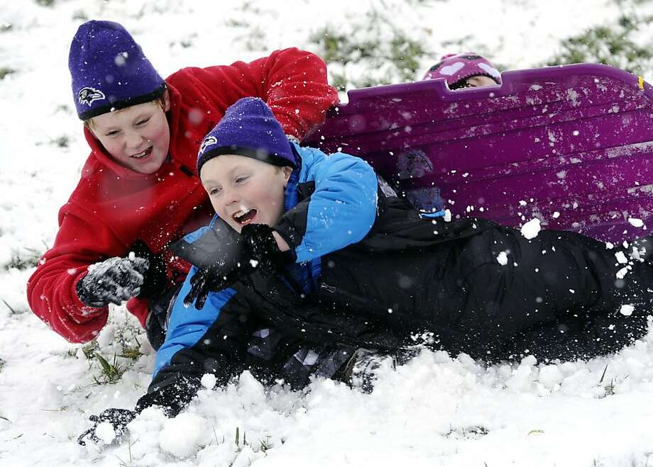 Austin and Evan Schmidt, crash-land their sled down a slope near their Springfield Township home on Saturday, Dec. 29, 2012, during the second snowfall in a week. Photo: Chris Dunn, Associated Press