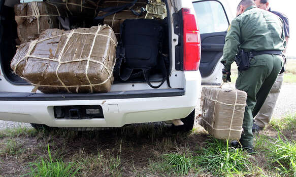 Dec. 19, 2012: A U.S. Border Patrol agent loads bundles of marijuana after a 300-pound bust in Jim Wells County just north of Falfurrias. The agents made the bust after a short car chase in which the suspects crashed an SUV into a mesquite tree and escaped. Photo: Jerry Lara, San Antonio Express-News / © 2012 San Antonio Express-News