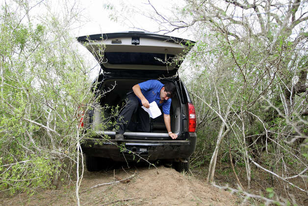 Brooks County Sheriff's Department Criminal Investigator Daniel Davila climbs out of a 2007 Suburban while looking for evidence at a ranch just north of Falfurrias, Texas, Wednesday, December 19, 2012. During a chase by another deputy, the man driving the vehicle crashed through a ranch gate and into the thick brush before jumping out and escaping. The reason for the evasive actions by the driver was not known. Photo: Jerry Lara, San Antonio Express-News / © 2012 San Antonio Express-News