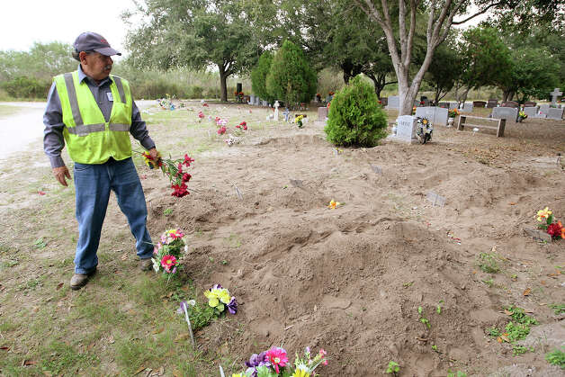 "Brooks County Cemetery worker Juan Villarreal removes old floral arrangements at ""John Doe"" burial plots in Falfurrias, Texas, Wednesday, December 19, 2012. So far this year, 127 bodies have been found in Brooks County this year and County Judge Raul M. Ramirez said that the county has run out of space at the cemetery for ""John Doe"" burials. Photo: Jerry Lara, San Antonio Express-News / © 2012 San Antonio Express-News"
