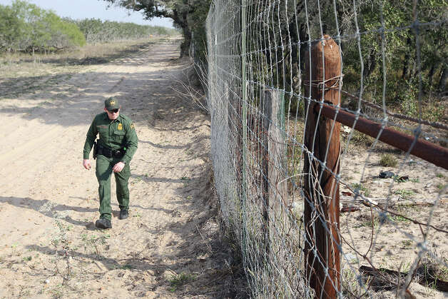 U.S. Border Patrol Agent Nicholas Ovington checks for tracks along a fence line at a ranch just south of Falfurrias, Texas, Wednesday, December 19, 2012. Immigrant apprehensions for the Rio Grande Sector, which includes Falfurrias, have surged by more than 40 percent for comparable 10-month periods in 2011 and 2012. Photo: Jerry Lara, San Antonio Express-News / © 2012 San Antonio Express-News