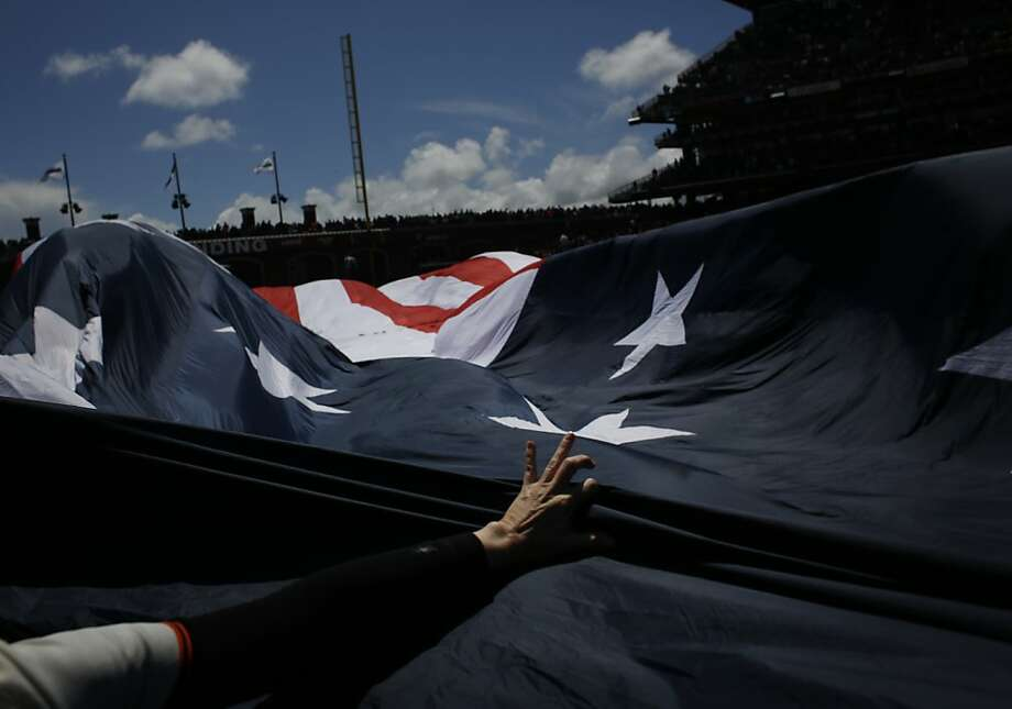 Dolores Flanagan of San Francisco tries to tame a giant American flag as it is unfurls on the field at the start of Giants season opener against the Pittsburgh Pirates at AT&T Park on Friday April 13, 2012. Photo: Mike Kepka, The Chronicle