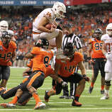 Valero Alamo Bowl, Dec. 29: Texas 31, Oregon State 27; Alamodome in San Antonio, Texas; Payout: $3,175,000 PHOTO: Texas quarterback David Ash (14) leaps over Oregon State defenders Tyrequek Zimmerman (08), Feti Unga (41) and Jordan Poyer (14) to score a touchdown in the second half of the Alamo Bowl.