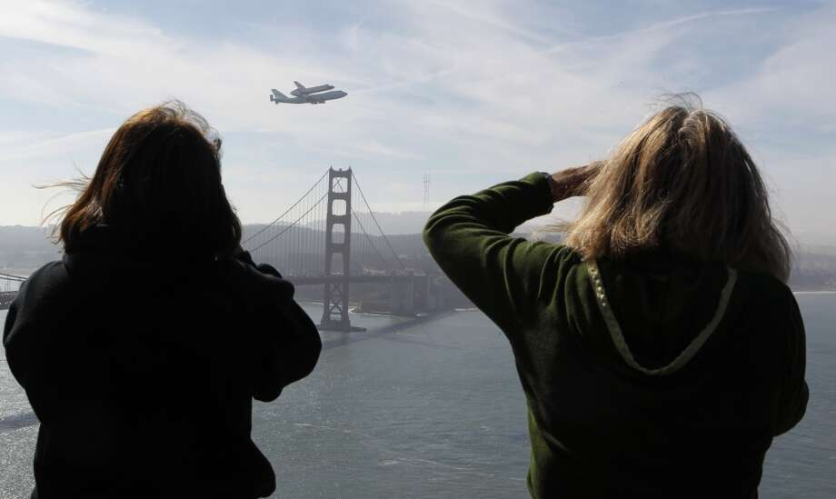 Nancy Crain (left) and Susette Stickel-Rufer take photos from the Marin Headlands in Sausalito, Calif.,  as the space shuttle Endeavour flies above the Golden Gate Bridge on its final flight before landing in Los Angeles on Friday, September 21, 2012. (Paul Chinn / The Chronicle)