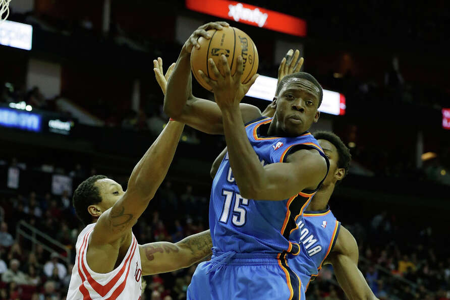Reggie Jackson #15 of the Thunder goes up for a rebound over Greg Smith #4 of the Rockets.