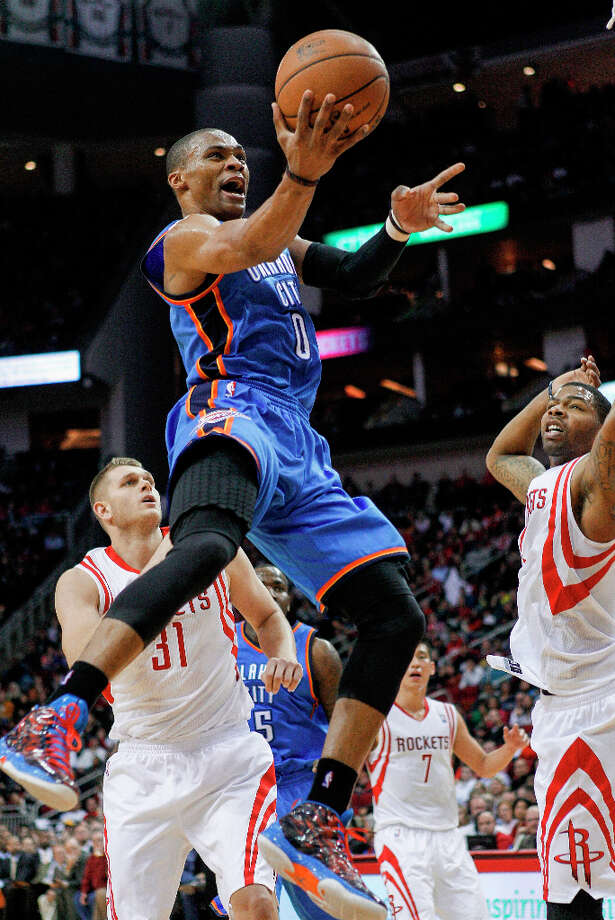Thunder guard Russell Westbrook (0) drives to the basket for a layup past Rockets center Cole Aldrich. Photo: BOB LEVEY, Associated Press / FR156786 AP