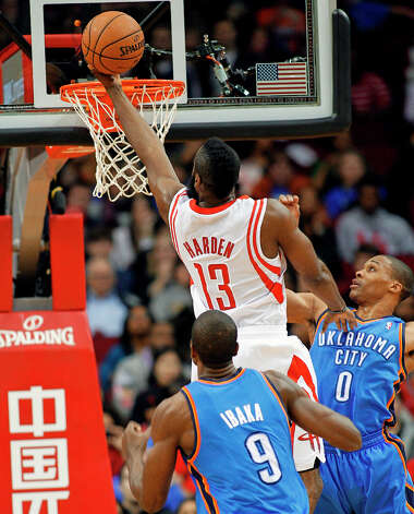 Rockets guard James Harden (13) drives to the basket between Russell Westbrook (0) and forward Serge Ibaka. Photo: BOB LEVEY, Associated Press / FR156786 AP