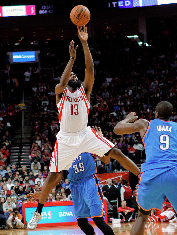 Rockets guard James Harden (13) releases a 3-point shot in front of Serge Ibaka. Photo: BOB LEVEY, Associated Press / FR156786 AP
