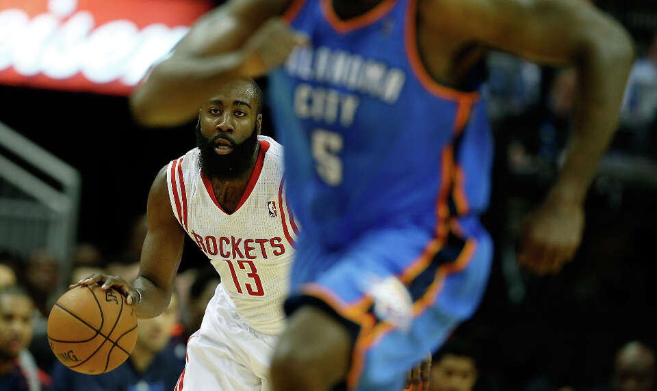 James Harden dribbles upcourt against Kendrick Perkins #5 of the Thunder.