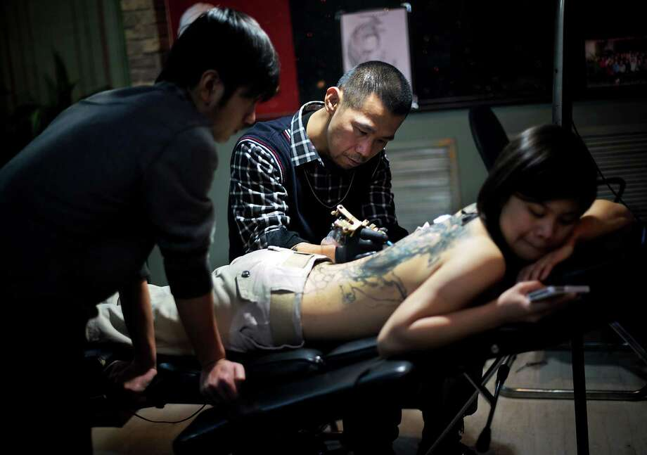 In this photo taken last week, a woman looks at a mobile phone as she is tattooed by an artist at a studio in Taiyuan in north China's Shanxi province. Tattoos has become a fashion statement in the communist country, as beauty and cosmetic surgery industry is booming in China. Photo: AP