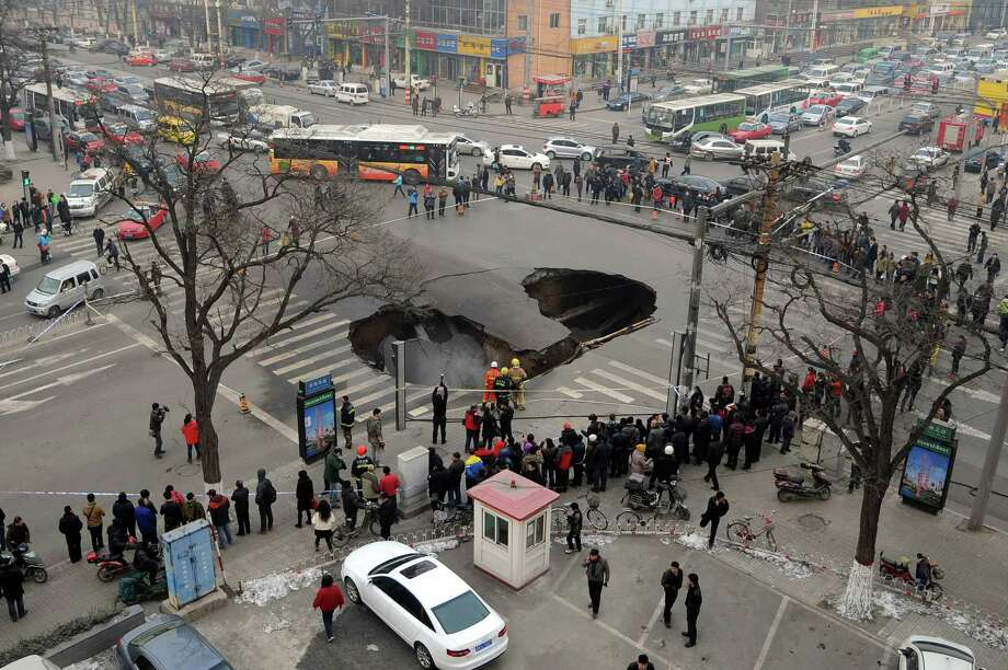 Shown Wednesday, the area around a sinkhole in the middle of a road junction is cordoned off in downtown Taiyuan, in northern China's Shanxi province. There is no report of injuries after the road caved in.  Photo: AP