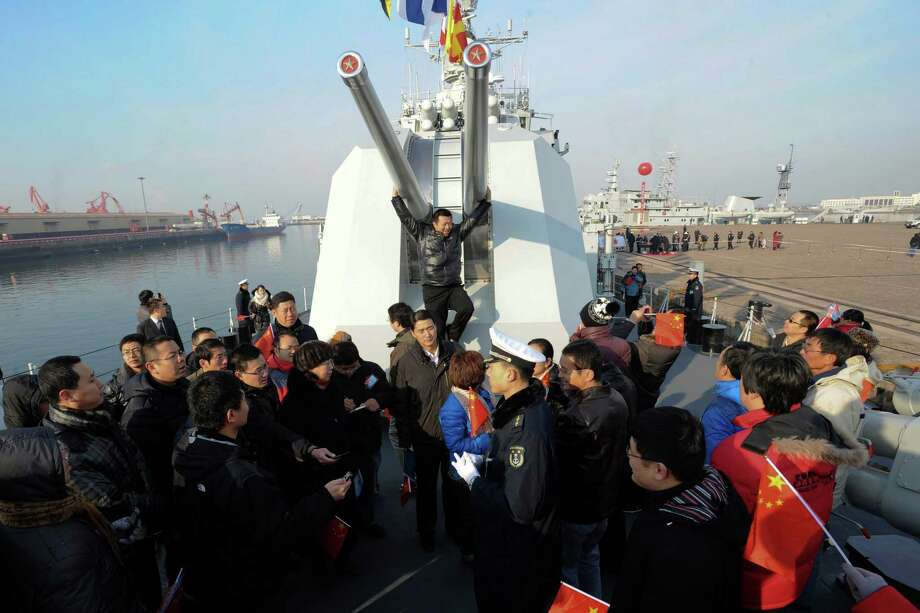 In this photo taken Wednesday a man, center in back, poses for a photo while others visit Chinese navy's missile destroyer Qingdao on the destroyer's public open day in Qingdao, in eastern China's Shandong province. Photo: AP