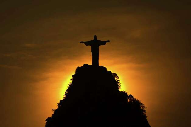 The sun sets behind the Christ the Redeemer statue and the Corcovado mountain in Rio de Janeiro, Brazil, Friday, Dec. 28, 2012. Rio de Janeiro recorded its hottest day on Wednesday since 1915 with a melting 43 C or 109.7 F. Photo: AP