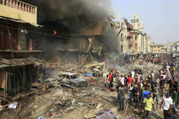 People gather at the site of a fire on Lagos Island in Lagos, Nigeria, on Wednesday. An explosion ripped through a warehouse Wednesday where witnesses say fireworks were  stored in Nigeria's largest city, sparking a fire. It wasn't immediately clear if anyone was injured in the blast that firefighters and locals struggled to contain. Photo: AP