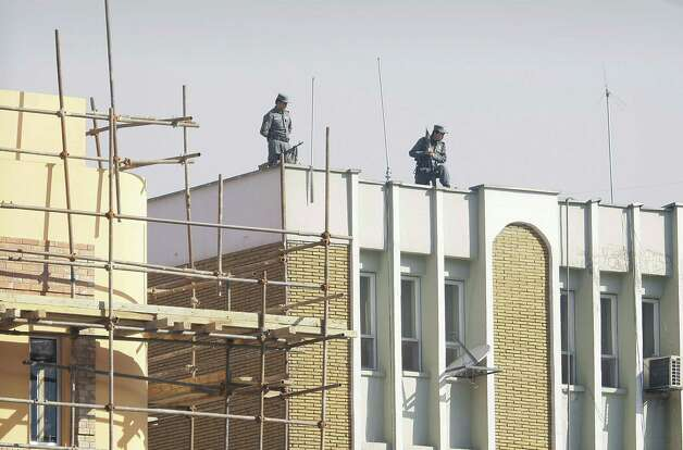 Afghan policemen watching down from top of the Kabul police headquarters, following the killing of an American advisor in Kabul, Afghanistan, Monday. An Afghan policewoman killed an American adviser at the Kabul police headquarters on Monday, a senior Afghan police official said. Photo: AP