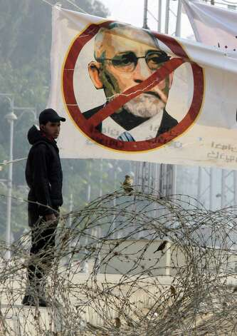 An Egyptian anti-riot soldier stands under a banner showing Muslim Brotherhood leader Mohammed Badie and barbed wire near the presidential palace in Cairo, Egypt, on Friday. The official approval of Egypt's disputed, Islamist-backed constitution held out little hope of stabilizing the country after two years of turmoil and Islamist President Mohammed Morsi may now face a more immediate crisis with the economy falling deeper into distress. Photo: AP