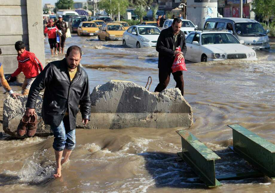 Iraqis make their way through flooded streets in Baghdad, Iraq, Thursday. An unusually heavy rainstorm has collapsed shoddy houses in Iraq, killing several people, police and health officials said Wednesday. Photo: AP