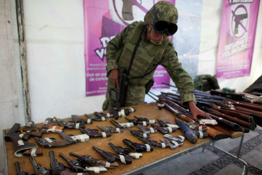 "A soldier organizes weapons that were handed over by their owners as part of a government program that exchanges weapons for bicycles, computers, tablets or money, on Christmas Eve in the Iztapalapa neighborhood of Mexico City, Monday. Mexico City is sponsoring a program after 10-year-old Hendrik Cuacuas was hit in the head by a 9-mm bullet during the Disney film ""Wreck-It Ralph"" in November. Photo: AP"