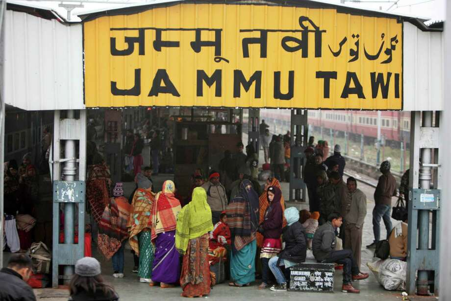 Indian passengers wrapped in woolen clothes wait at a train station on a cold and foggy morning in Jammu, India, Wednesday. Many trains are running behind scheduled due to poor visibility caused by fog and severe cold wave which has disrupted normal life in north India. Photo: AP
