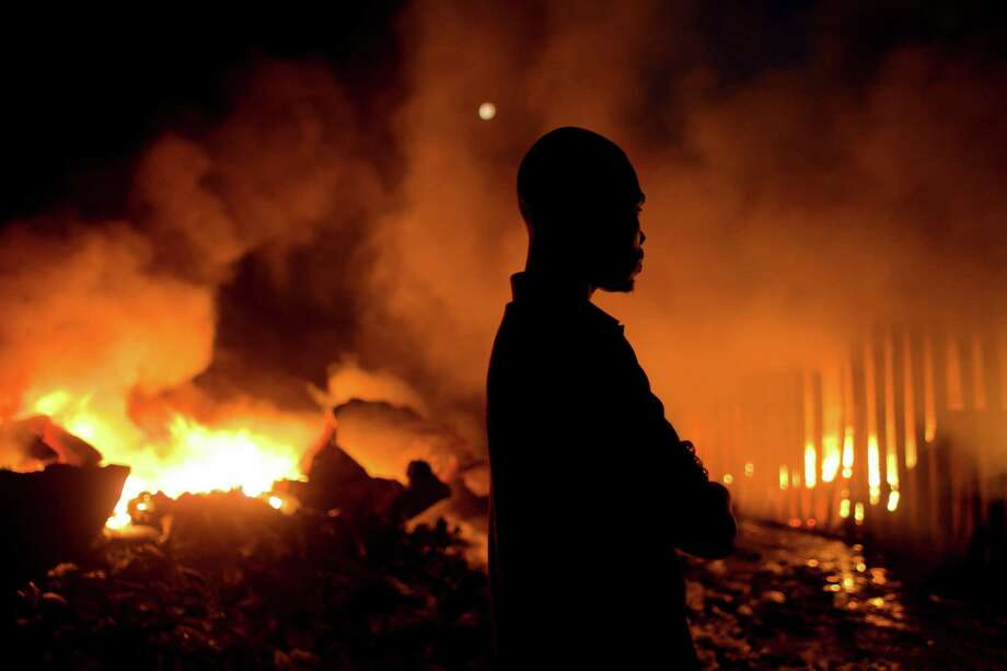 A merchant watches flames engulf  Port Market, where his merchandise was stored, in Port-au-Prince, Haiti, Saturday. Police spokesman Frantz Lerebours said Saturday that dozens of stalls at the popular marketplace were burned to the ground and that few items were recovered. Authorities are investigating what caused the late Friday fire. Photo: AP