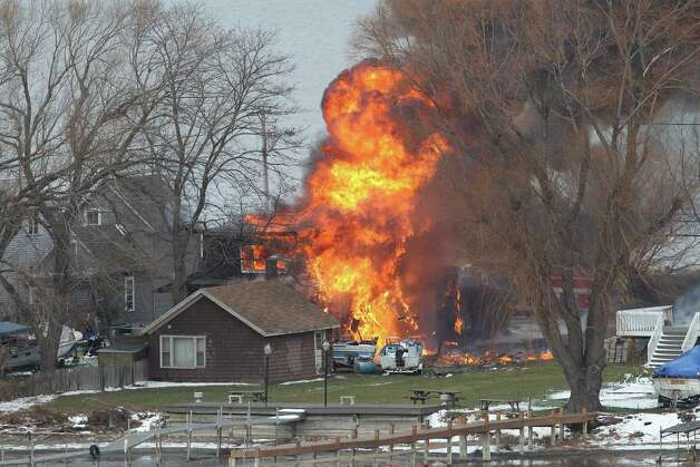 A house burns Monday in Webster, New York. A former convict set a house and car ablaze in his lakeside New York state neighborhood to lure firefighters then opened fire on them, killing two and engaging police in a shootout before killing himself while several homes burned. Authorities used an armored vehicle to evacuate the area. Photo: AP