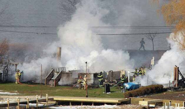 Firefighters battle a blaze after they were let back in Monday in Webster, N.Y. A gunman ambushed four volunteer firefighters responding to an intense pre-dawn house fire Monday morning outside Rochester, N.Y., killing two and ending up dead himself, authorities said. Police used an armored vehicle to evacuate more than 30 nearby residents.  Photo: AP