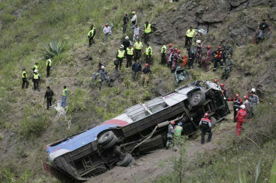 Police officers and rescuers surround a crashed bus in La Joaquina, Ecuador on Wednesday. Police say that the bus lost its brakes, flipped over and tumbled down an embankment, killing at least 13 people and injuring another 37. Photo: AP