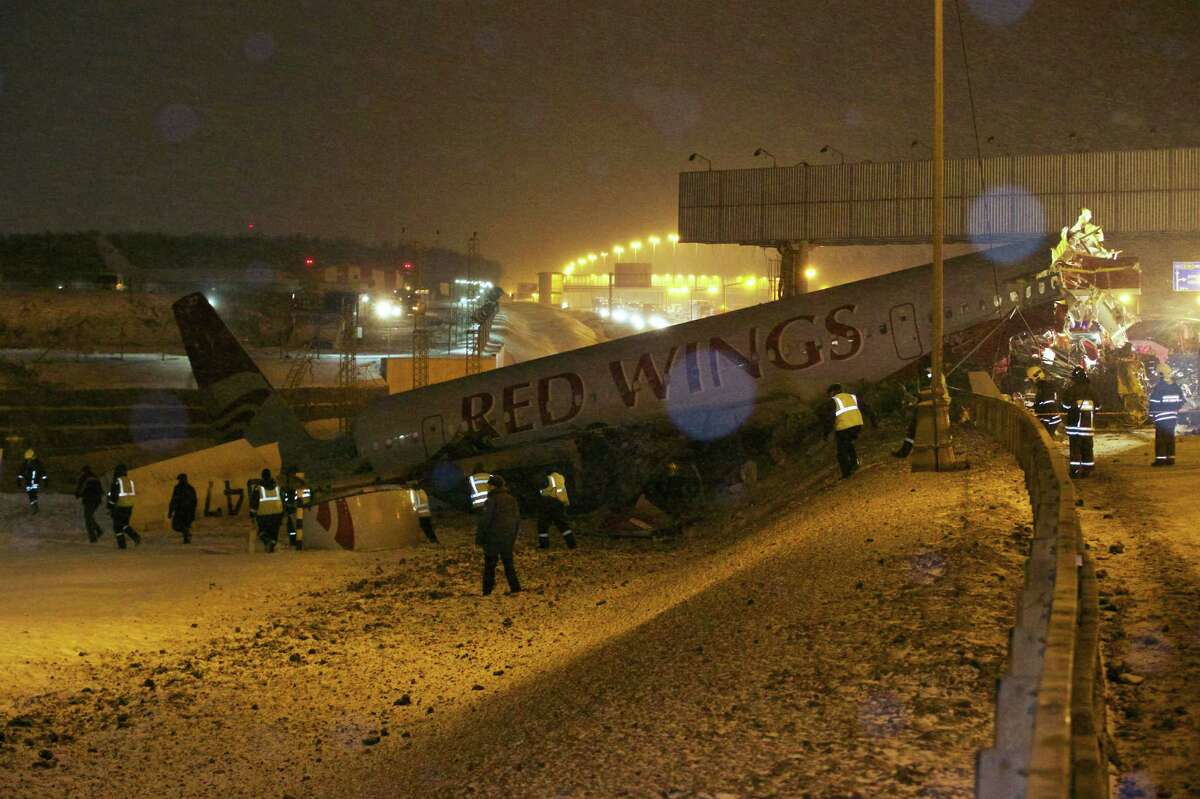 Rescuers work at the site where a plane careered off the runway at Vnukovo Airport in Moscow on Saturday. A Tu-204 aircraft belonging to Russian airline Red Wings careered off the runway at Russia's third-busiest airport on Saturday, broke into pieces and caught fire, killing several people.