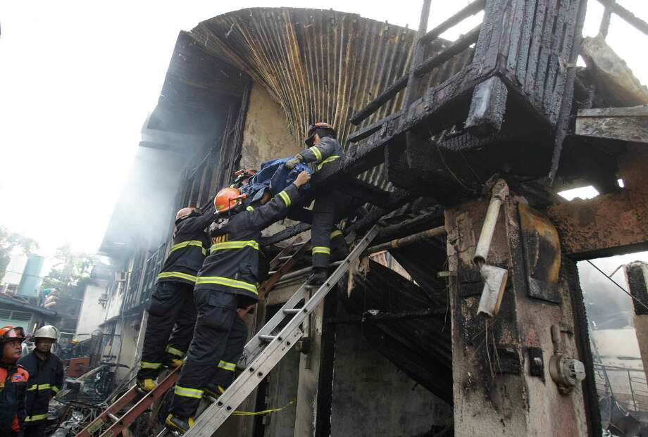 Filipino firemen bring down a body from the second floor after a fire hit a row of apartments in suburban Quezon City, north of Manila, Philippines on Christmas day, Tuesday. Fire Officer 3 Francisco Mabunga said about 6 people died when a row of houses went up in flames early Christmas day Tuesday. Another fire hit a slum area in San Juan city leaving some 2,000 families homeless. Photo: AP
