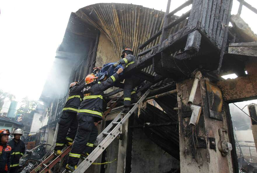 Filipino firemen bring down a body from the second floor after a fire hit a row of apartments in sub