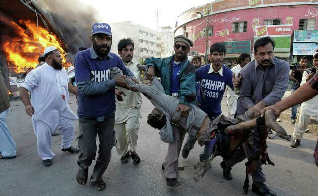 Pakistani volunteers carry a wounded bus passenger following a blast in Karachi, Pakistan on Saturday. The blast that ripped through the bus  set the vehicle on fire and reduced it to little more than a charred skeleton, killing scores of people and left many injured. Police were trying to determine whether the explosion was caused by a bomb or a gas cylinder, said police spokesman. Many buses in Pakistan run on natural gas. Photo: AP