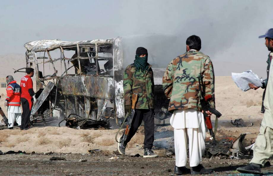 Security men gather at the site of a suicide bombing in Quetta, Pakistan, on Sunday. A suicide bomber driving a vehicle packed with explosives rammed into a bus carrying Shiite Muslim pilgrims in southwest Pakistan on Sunday, killing several people, a government official and eyewitnesses said. Photo: AP