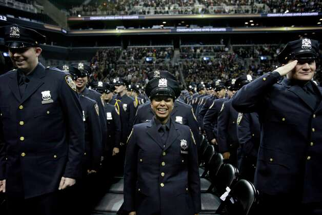 A new police officer laughs during a police academy graduation ceremony in New York, on Friday.  The number of New York City murders is expected to hit a record low this year, and shootings are at their lowest point in at least 18 years. Photo: AP